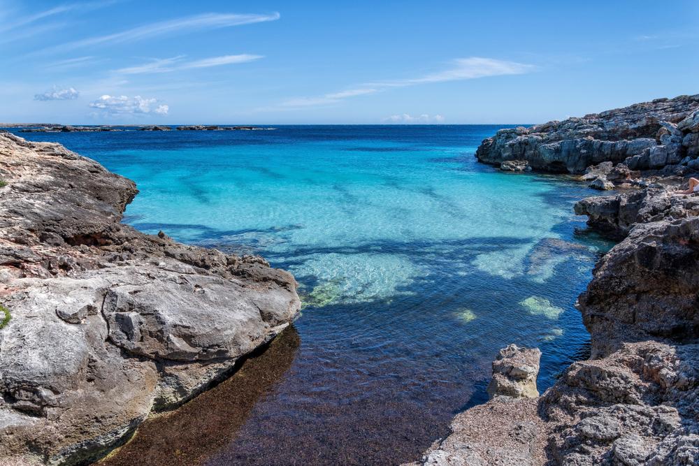 Cala en Binibeca en Menorca. Agua turquesa y roca.