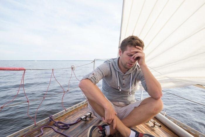 Hombre mareandose al mar